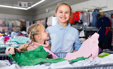 Two small happy cheerful positive smiling sisters satisfied with purchases in children clothing shop Stock Photo