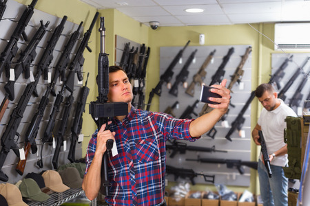 Young man is taking selfie on phone with air gun in airsoft shop.  Stock Photo