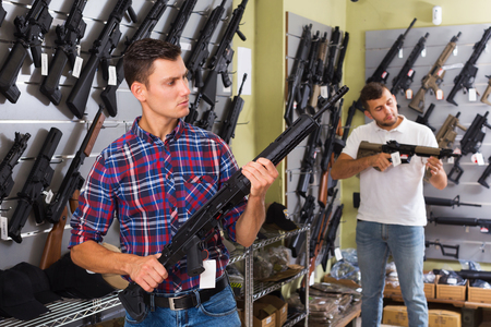 two concentrated male friends choosing air-powered gun in army market Stock Photo