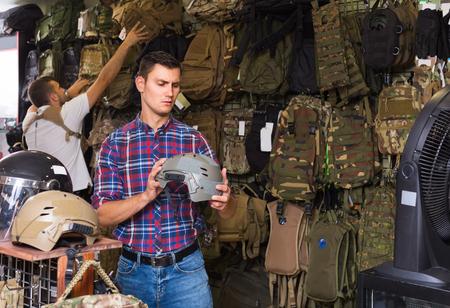 Young positive italian guys choosing helmet in military shop