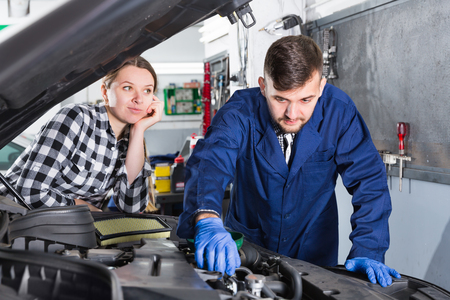 Young female master with foreman are replacing the oil in the car at workshop