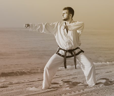Young  guy demonstrates taekwondo poses at seaside in sunset outdoor