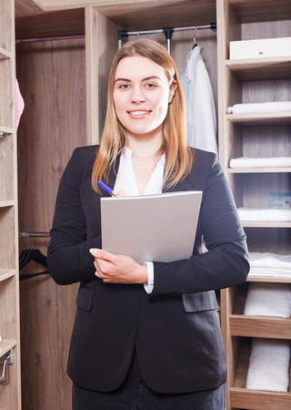 Portrait of young successful woman sales manager in furniture salon, standing with clipboard in interior of dressing room