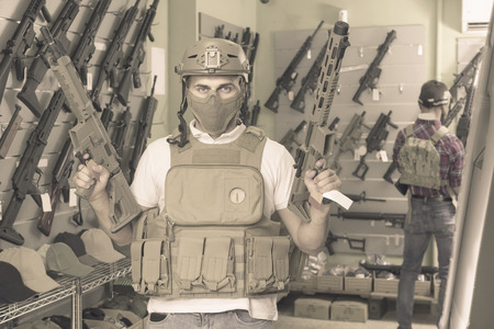 Young positive germany guys in military equipment with rifle in airsoft shop