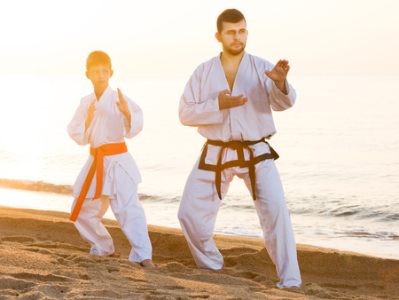 Glad man and boy exercising karate in morning outdoor