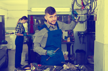 Man is posing on his workplace in time repair cars in workshop.