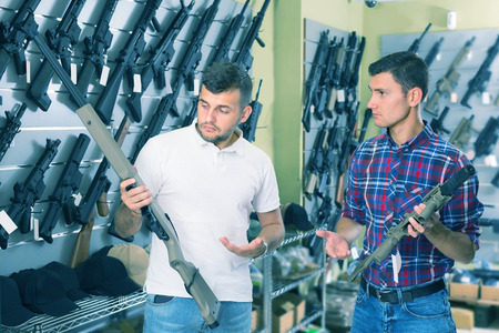 Two friends are choosing pneumatic rifle in airsoft store.