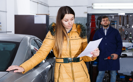 Female is dissatisfied of tire winter replacement of her car in workshop.