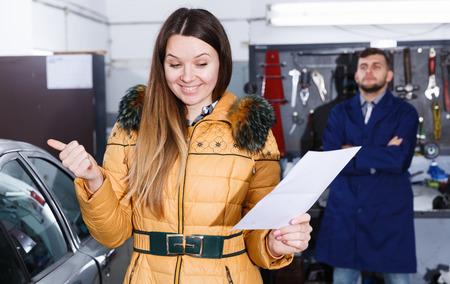 Woman client is satisfied of repair of her car in winter in workshop.