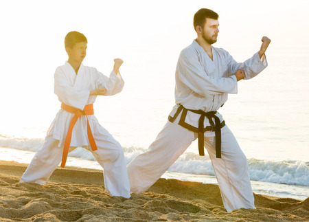 Active positive young man and boy exercising karate in morning outdoor