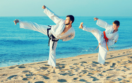 Active positive man and boy exercising karate in morning outdoor