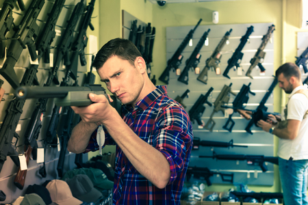 Positive young men buying air weapon in military shop