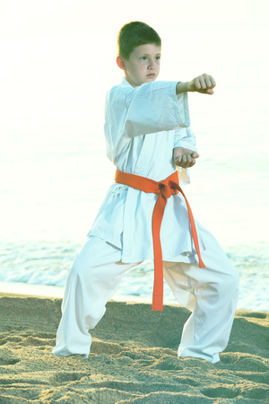 Young boy practicing karate positions at ocean beach