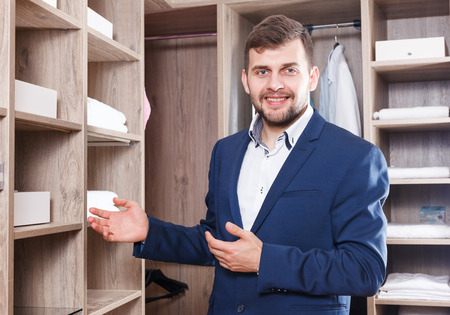 Young successful sales manager demonstrating modern dressing room in furniture salon