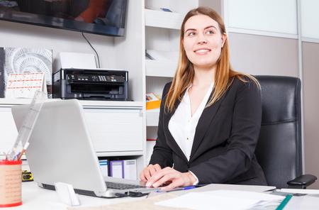 Smiling salesgirl of furniture materials using laptop at workplace in showroom