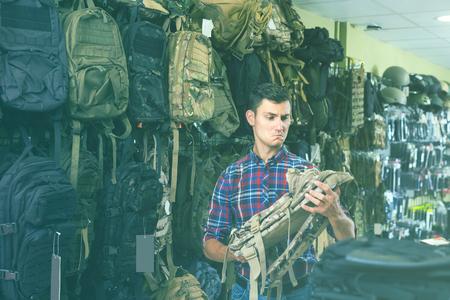 positive man choosing textile backpack gun in military shop