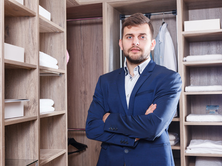 Portrait of young successful confident sales manager standing in interior of dressing room in furniture salon Stock Photo
