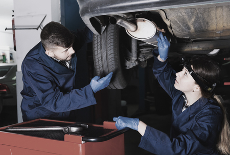 Two glad  cheerful positive  masters are repairing car in workshop. Stock Photo