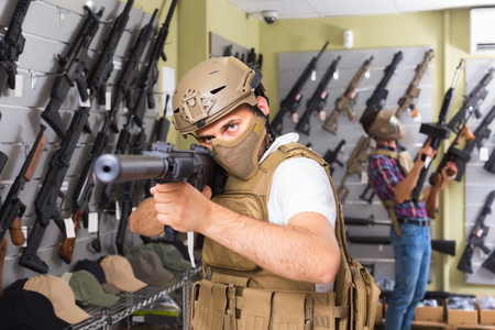 Young positive european  guys in military equipment with rifle in airsoft shop