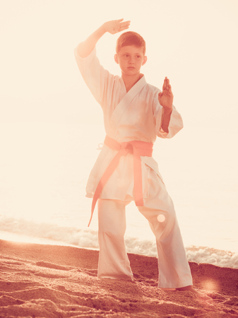 Young boy practising karate poses at seaside in sunset outdoor Stock Photo