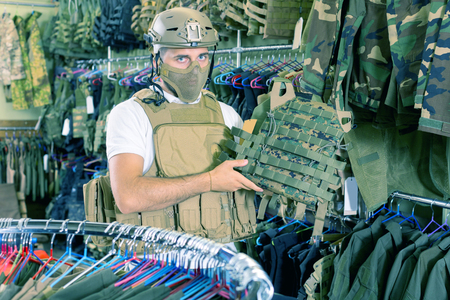Portrait adult male customer try on ammunition with rifle in army store Stock Photo