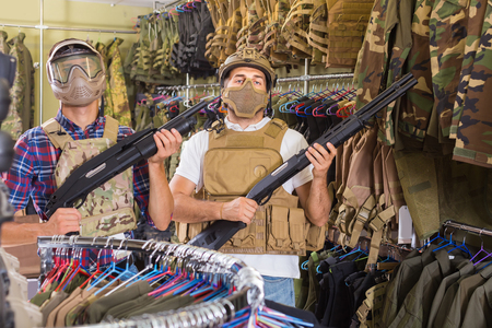 Young positive guys in military equipment with rifle in airsoft shop