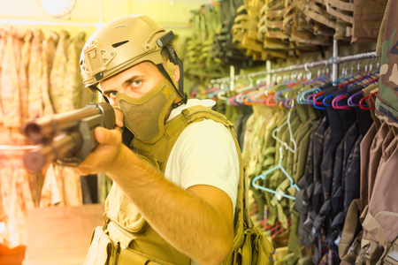 germany adult guy in military equipment with weapon in army shop Stock Photo