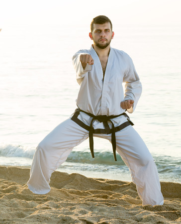 Young  guy practising  aikido poses at seaside in sunset outdoor