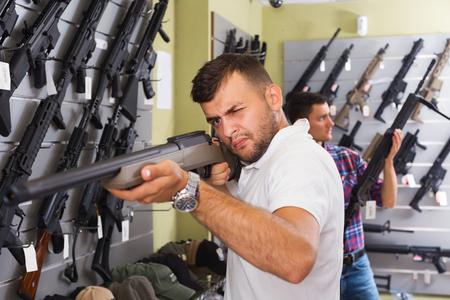 two adult friends choosing air-powered gun in army market