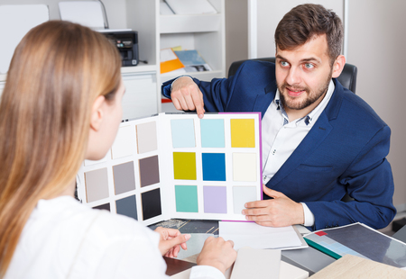Ordinary girl planning new furniture in her house in furniture salon