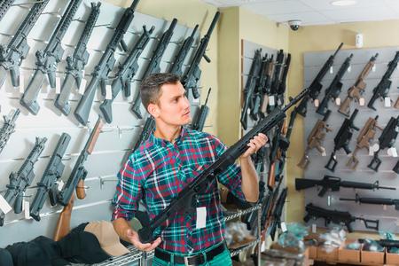 Young man is choosing air-powered gun in army market.