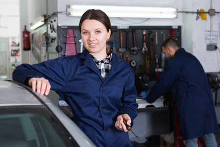 Portrait of female who is standing on her workplace in workshop. Stock Photo
