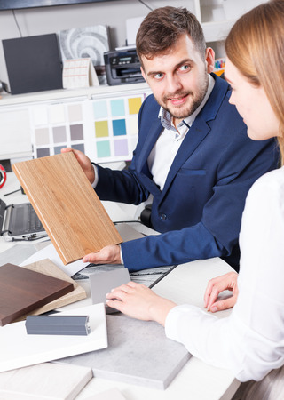 Young woman with salesman choosing material for new furniture in salon Stock Photo