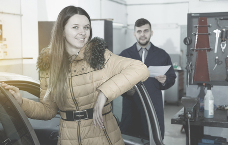 Young woman is satisfied of tire replacement of her car in winter in workshop. Stock Photo