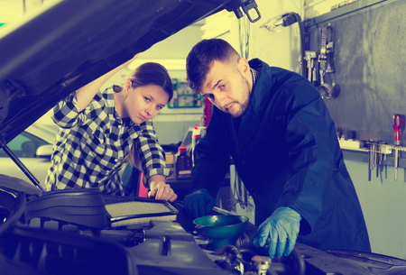 positive young female and man master are standing near car and replacing the oil in workshop. Stock Photo