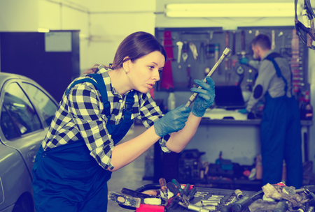 Young  pleasant  woman master is choosing instruments for work in workshop. Stock Photo