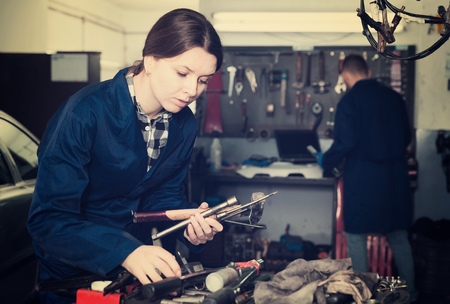 Young woman is choosing instruments for repair car in workshop  Stock Photo