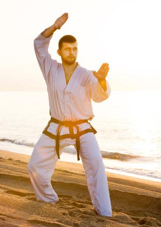 Man doing karate at ocean quay in dawn