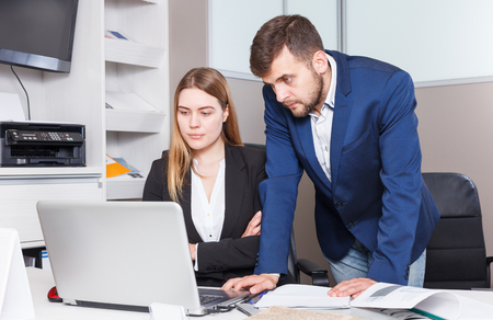 Young female and male sales managers of furniture salon working on laptop  Stock Photo