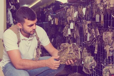 adult american man choosing holster for gun in military shop