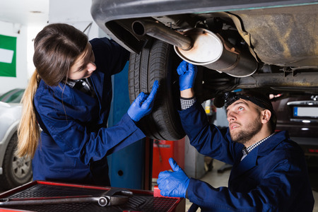 Two masters are repairing car on their workplace in workshop Stock Photo