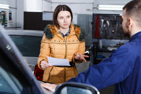 Young woman is disappointed of tire replacement of her car in winter in workshop.