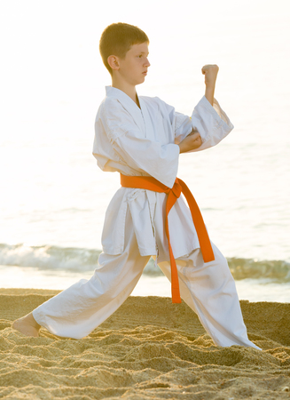 Young boy practicing karate poses at ocean beach