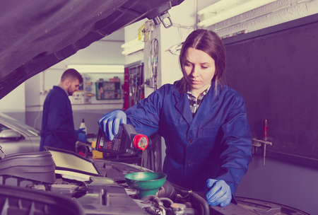 adult positive female is standing near car and replacing the oil in workshop.