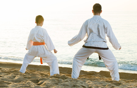 Positive young man and boy exercising karate in morning outdoor