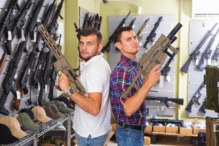 Two young men choosing air gun in military store Stock Photo