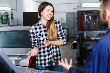 Young woman is satisfied of tire replacement of her car in spring in workshop. Stock Photo