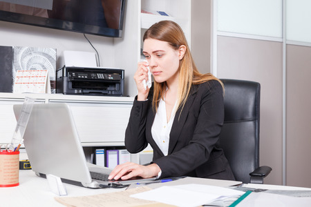 Disappointed young business woman working on laptop in salon
