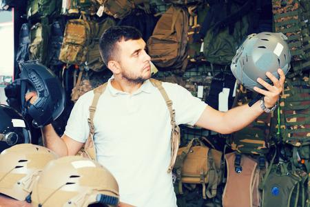 Young positive european guys choosing helmet in military shop