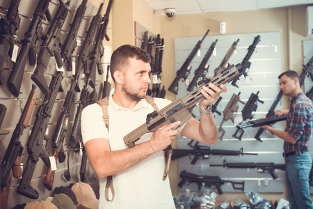 Two young men selecting air weapon in military shop